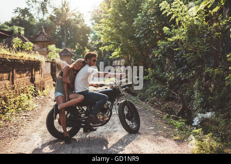 Loving young couple on a motorcycle. Young man and woman on motorbike in a village on a summer day. - Stock Photo