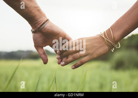 Horizontal shot of young couple walking through meadow holding hands with focus on hands . - Stock Photo