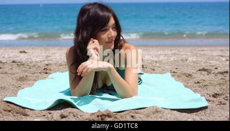 Pretty woman sunbathing on a tropical beach - Stock Photo