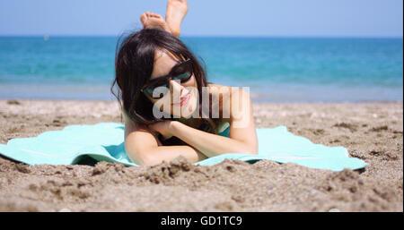 Pretty woman in sunglasses sunbathing on a beach - Stock Photo