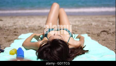 Woman suntanning on a tropical beach in summer sun - Stock Photo