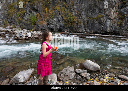 Young girl blowing bubbles along the Little Susitna river near Hatcher Pass, Southcentral Alaska, autumn - Stock Photo