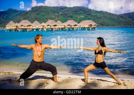 Couple doing yoga in front of overwater bungalows, Le Taha'a Resort, Tahiti, French Polynesia, South Pacific, Pacific - Stock Photo