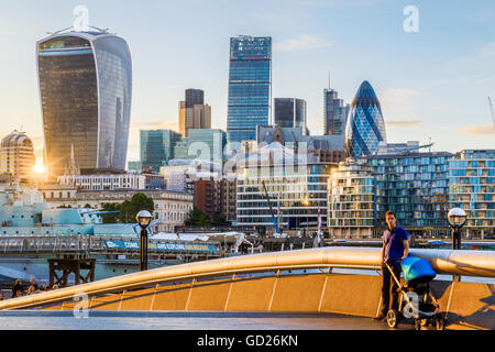 London, UK - June 24, 2016 - A young father with a baby pram against a background of London financial district at - Stock Photo