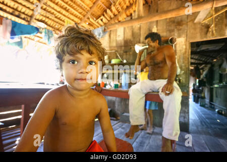 Amazonas, Brazil - August 14, 2008: Young boy and his father in a wooden a house on the Amazon River bank. - Stock Photo