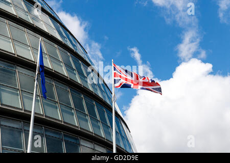 The European Union (EU) flag and waving British Union flag at City Hall against blue sky. - Stock Photo