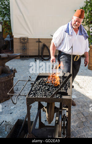 Friedberg, Germany - July 09, 2016: A man dressed in traditional costume is working as a blacksmith in the traditional - Stock Photo