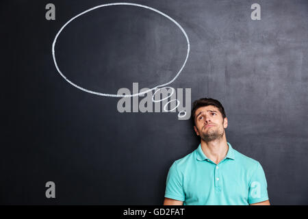 Unhappy despaired young man over blackboard background with blank speech bubble - Stock Photo