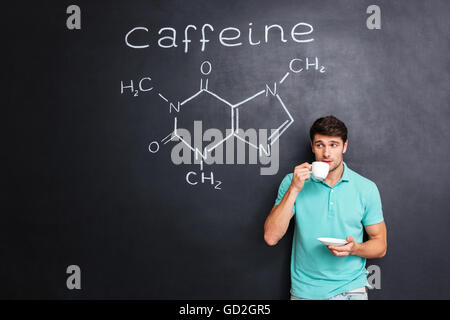 Handsome young man drinking coffee over blackboard background with drawn chemical structure of caffeine molecule - Stock Photo