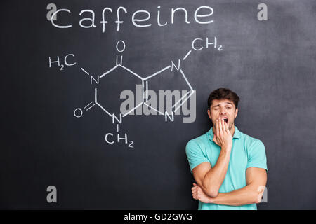 Exhausted fatigued young man yawning over chalkboard background with drawn chemical structure of caffeine molecule - Stock Photo
