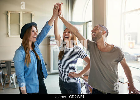 Laughing young business entrepreneurs in informal trendy clothing standing celebrating a success giving a high fives - Stock Photo