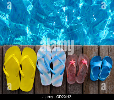 Brightly colored flip-flops of the family on wooden background near the pool. Summer travel and vacation concept - Stock Photo