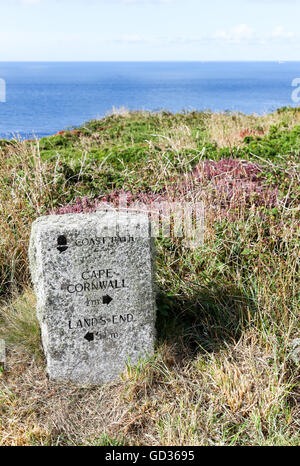 A stone sign post saying Cape Cornwall 1/2 mile Lands End 5 1/4 miles on the South West Coast path near Cape Cornwall - Stock Photo