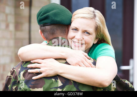Portrait Of Wife Hugging Army Husband Home On Leave - Stock Photo