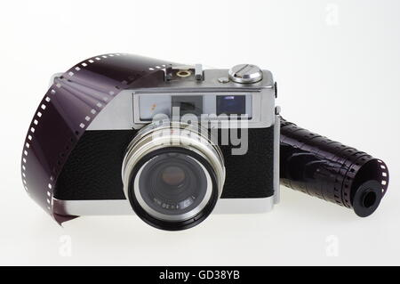 Old rangefinder analog camera system 135 and the photographic film on the white background. - Stock Photo