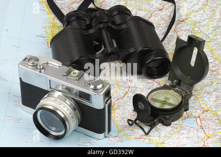 Porro binoculars, military compass and old rangefinder analog camera lying on the map. - Stock Photo