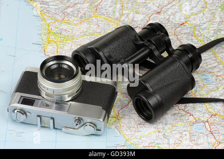 Porro binoculars and old rangefinder analog camera lying on the map. - Stock Photo