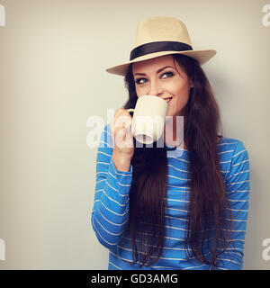 Happy woman in straw hat drinking coffee with thinking face looking up. Toned portrait - Stock Photo