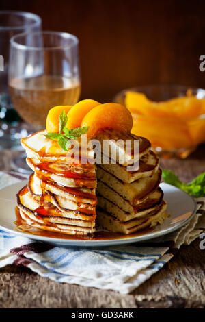 Stack of homemade pancakes with poached peaches - Stock Photo