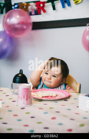 A child, a one year old girl at her birthday party, sitting in a high chair at a table. - Stock Photo