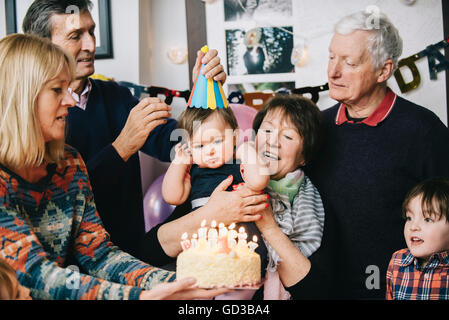 A family gathered to celebrate a one year old girl's birthday party. A cake with lots of candles. - Stock Photo