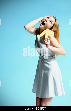 Beautiful girl in a white dress holding two arrows - Stock Photo