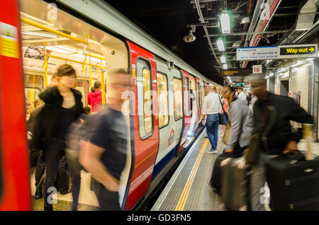 Passengers disembark and board a London Underground train at Victoria Station. - Stock Photo