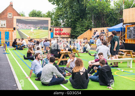 People talking and drinking while watching Wimbledon tennis match in a big outdoor screen in Pop Fields, Brixton
