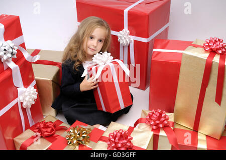 Little girl sitting surrounded by a huge pile of Christmas gift boxes - Stock Photo