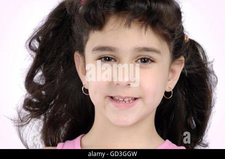 Portrait of a five year old girl with dark curly hair - Stock Photo