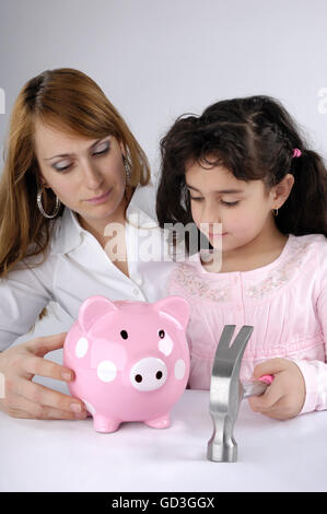 Mother with her young daughter intending to break a piggy bank - Stock Photo