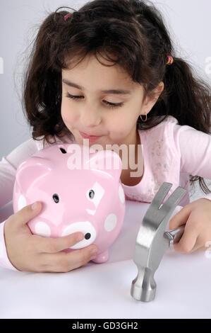 Young girl intending to break a piggy bank - Stock Photo