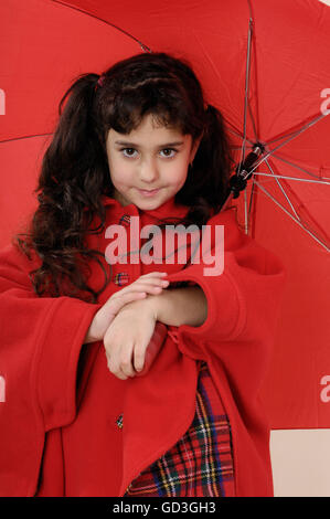 Five year old girl in a red coat with an umbrella - Stock Photo
