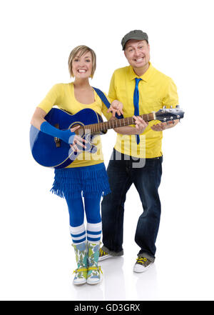 Happy young couple, woman playing the guitar and man standing beside her - Stock Photo