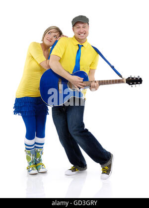 Happy young couple, man playing the guitar and woman standing beside him - Stock Photo