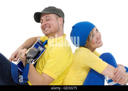Happy young couple, man playing the guitar and woman sitting beside him - Stock Photo