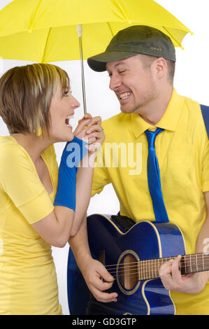 Happy young couple with a guitar under an umbrella - Stock Photo