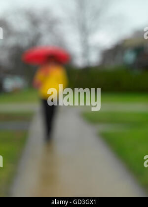 Woman with an umbrella on a sidewalk in the rain, blurred - Stock Photo