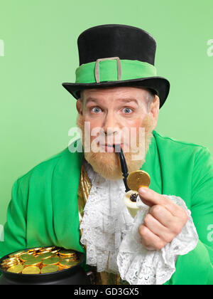 Leprechaun in bright green clothes holding a golden coin in his hand - Stock Photo