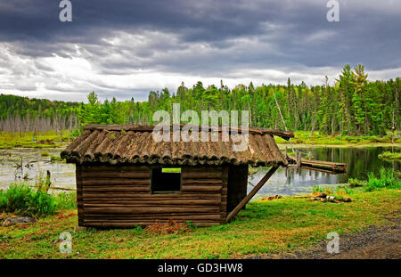 Old and abandoned log cabin in Temagami in front of a beaver dam and forest. - Stock Photo