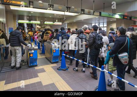 Passengers standing in queue get railway platform, tokyo, japan - Stock Photo