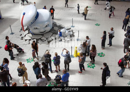 London, UK. 12th July 2016.   The Giant Marshmallow man breaking through the floor of Waterloo station  has become - Stock Photo