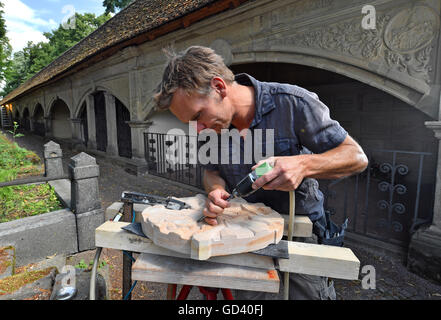 Sculptor Martin Roedel working on a sandstone relief in front of the arcade arches at Stadtgottesacker in Halle/Saale, - Stock Photo