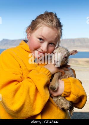 Girl holding a newborn lamb, Iceland - Stock Photo