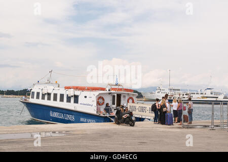 Corfu Port - tourists waiting by the small Kamelia Lines ferry that will take them to the tiny unspoilt Greek island - Stock Photo