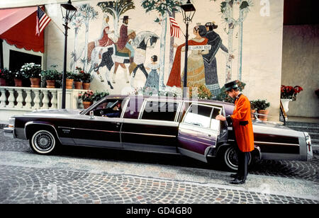 A doorman in red coattails welcomes guests in a long limousine to the Beverly Wilshire, a world-class hotel located - Stock Photo
