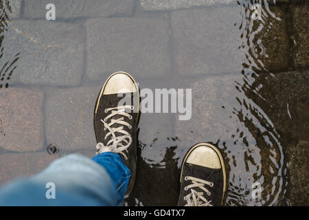 Male legs in sneakers and blue jeans walking through the rain puddle, top view - Stock Photo