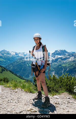 Smiling pretty young adult woman in shorts and helmet hiking in the mountains under clear sky - Stock Photo