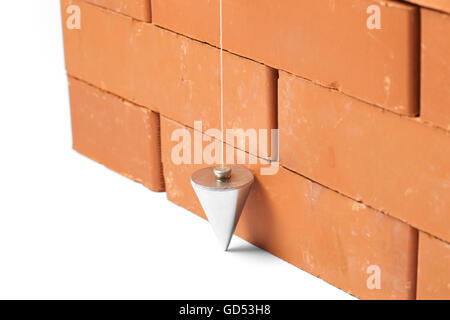 Bricks in masonry with touched plum bob for vertical line isolated on white background - Stock Photo