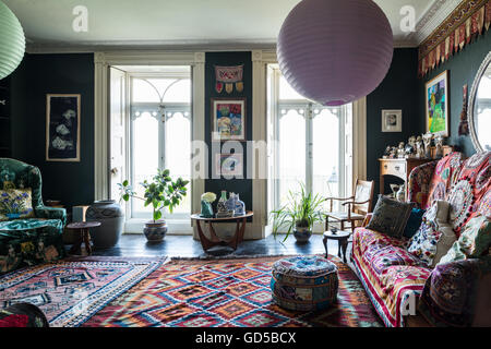 Large kilim in Regency drawing room painted in Sherwood Green by Farrow & Ball. The jacobean style high back sofa - Stock Photo
